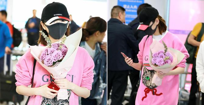 景甜捧鲜花装扮粉嫩 不停玩手机似在电话传情