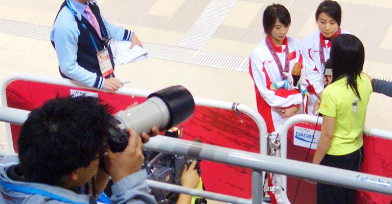 2006年12月11日,第十五届多哈亚运会跳水女子双人三米板,郭晶晶夺冠。绯闻男友霍启刚出现在泳池左侧看台上vip区域,一身休闲打扮的霍启刚就坐在第一排,他的腿上还放着一架摄影师常用的专业相机。每当郭晶晶和李婷从楼梯走上跳板时,霍启刚就会举起腿上的相机,将镜头对准郭晶晶。走板、跳跃、入水……一整套动作结束,他才意犹未尽地放下相机,然后转头望向左侧地大荧幕。